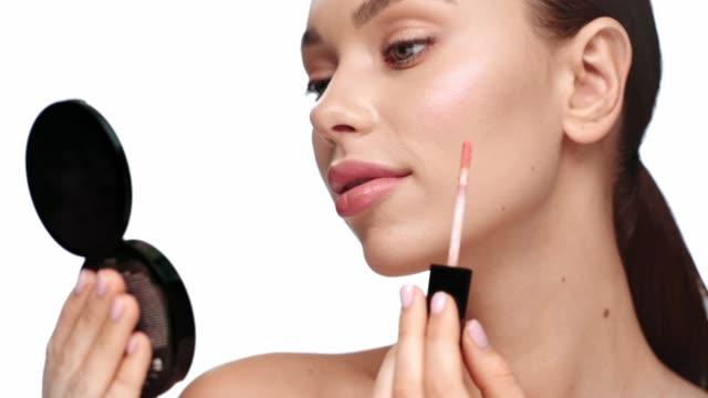 白に隔離されたリップバームを適用する笑顔の女性 - リップクリーム点の映像素材/bロール