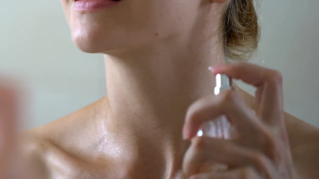 smiling woman applying perfume on neck in bathroom, special scent for lady - profumato video stock e b–roll