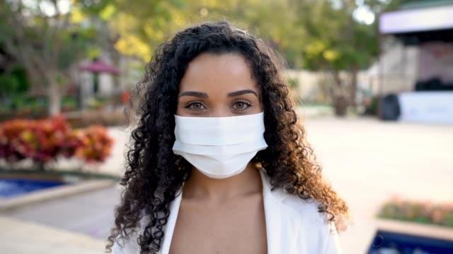 vídeos de stock e filmes b-roll de smiling woman behind face protection mask - afro latino mask