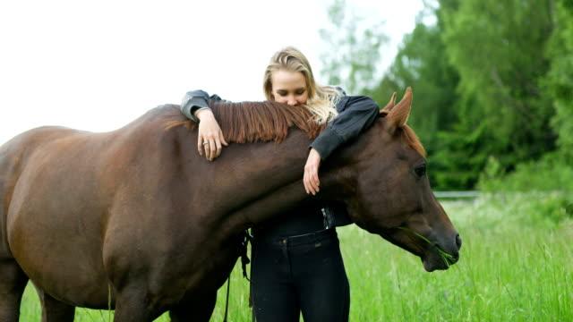 Femme souriante caressant son cheval arabe dans le domaine - Vidéo