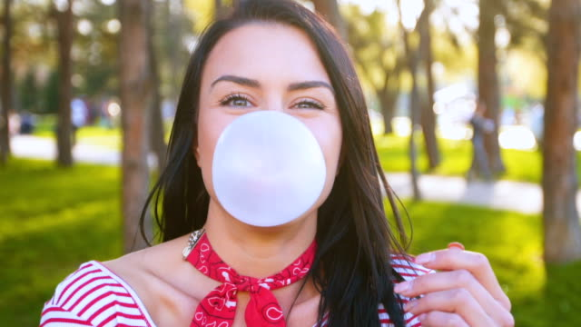 smiling woman chewing gum and blowing bubble - gum стоковые видео и кадры b-roll