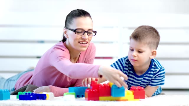 Smiling woman child psychologist and baby boy playing with colorful constructor block lying on floor video