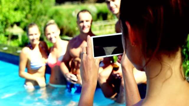 Smiling woman clicking photos of friends from mobile phone near poolside video