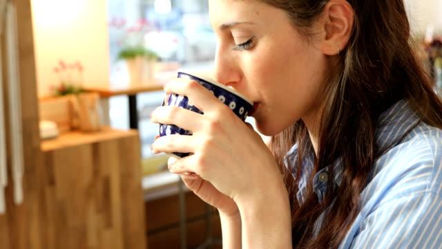 vídeos y material grabado en eventos de stock de sonriente mujer tomando café en la cafetería - café bebida