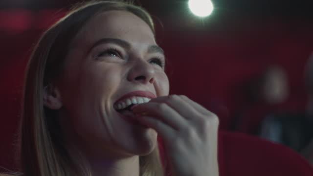 smiling woman eating popcorn in cinema - pop corn video stock e b–roll