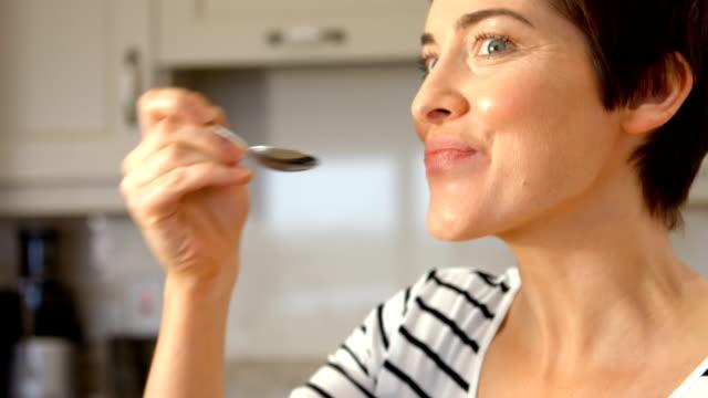 Smiling woman eating yogurt Smiling woman eating yogurt in the kitchen spoon stock videos & royalty-free footage