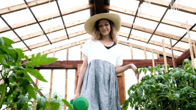 sera sulama olabilir ile gülümseyen kadın çiftçi bir hasır şapka ve kıyafet gider - bahçe ekipmanları stok videoları ve detay görüntü çekimi
