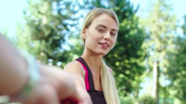 smiling woman flirting with man in park. happy couple walking in summer park - podążać za czynność ruchowa filmów i materiałów b-roll