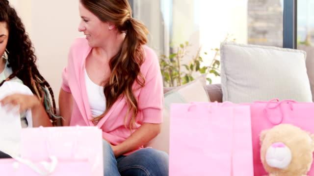 vidéos et rushes de femme souriante, donnant présent pour lesbiennes couple de leur nouvelle enfant - fête de naissance