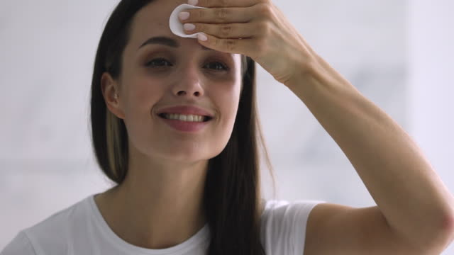 Smiling woman holding cotton pad cleansing face skin with cleanser Smiling young woman hold cotton pad disk cleansing clean face skin with cleanser, happy attractive girl remove make up looking in mirror enjoy healthy beauty treatment skincare concept, close up view padding stock videos & royalty-free footage