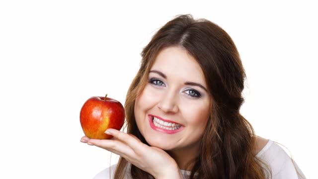 笑顔の女性が分離したリンゴ果実を保持します。 ビデオ