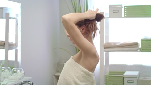 Smiling woman in bath towel making hair tail front mirror in bathroom