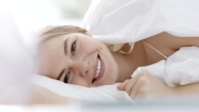 leende kvinna i sängen - duntäcke bildbanksvideor och videomaterial från bakom kulisserna