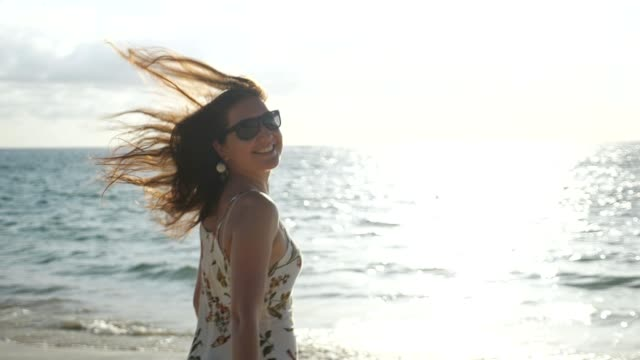 smiling woman in dress runs along empty sea beach to waves smiling young girl in summer dress runs along empty beach to ocean waves on sunset slow motion short length stock videos & royalty-free footage
