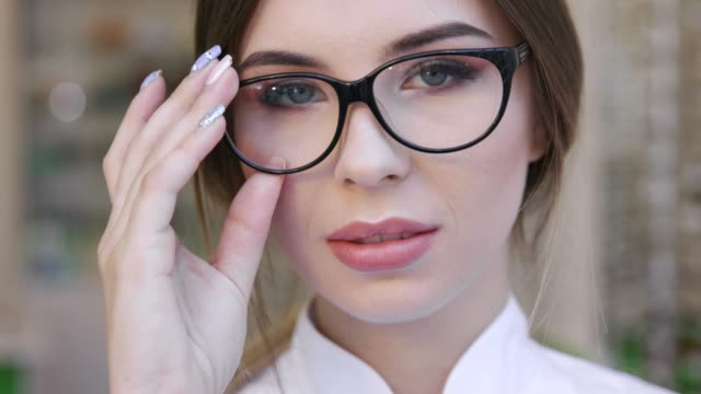 smiling woman in eyeglasses in optical shop closeup - optometrist stock videos and b-roll footage