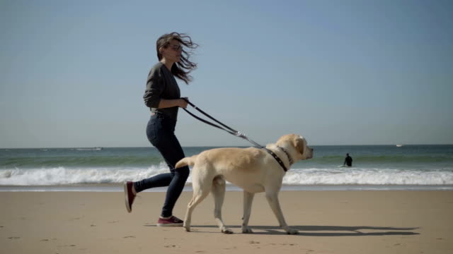 Smiling woman in eyeglasses running with labrador on beach.