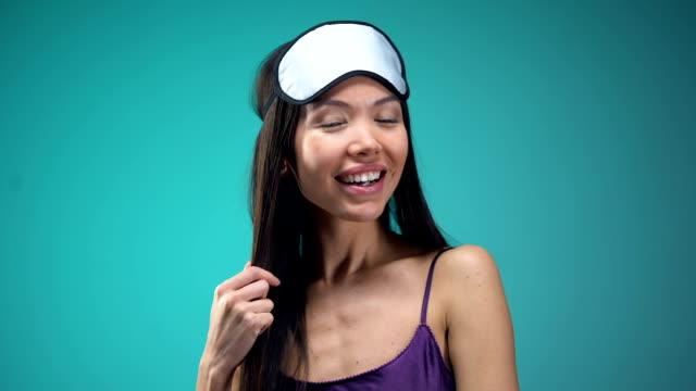 Smiling woman in pajamas wearing blindfold on eyes, going to sleep, nighttime