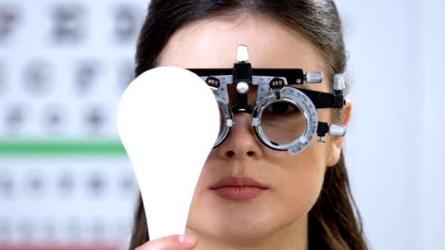 vidéos et rushes de femme de sourire dans le phoropter fermant un oeil, examen de vision, bilan de santé - réfracteur