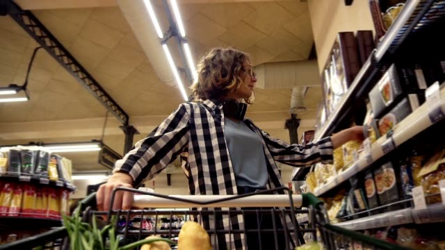 Smiling woman in plaid shirt and headphones on neck is walking in grocery store steering shopping trolley with food inside. Standing in front shelves with assortment, take a jar and put it to a cart. Low angle footage from the cart video