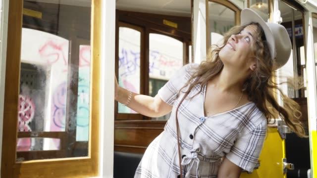 vídeos de stock e filmes b-roll de smiling woman in vintage tram on street - eletrico lisboa