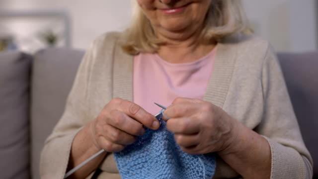 улыбающаяся женщина вязание, заботливая бабушка делает подарок внуку, хобби, крупным планом - шарф стоковые видео и кадры b-roll