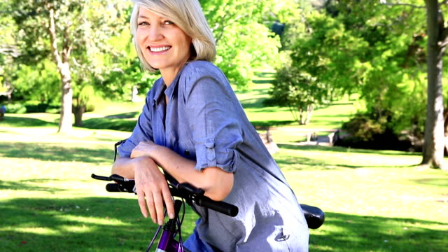 Smiling woman leaning on her bike video