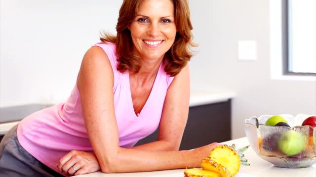stockvideo's en b-roll-footage met smiling woman leaning on kitchen counter - vrouwelijkheid