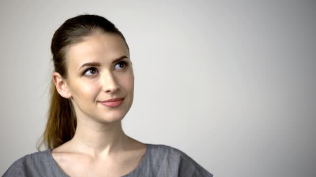 smiling woman looking at camera - distrarre lo sguardo video stock e b–roll