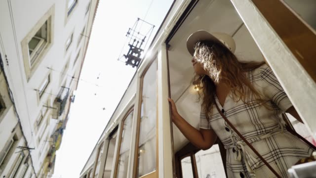 vídeos de stock e filmes b-roll de smiling woman looking away from vintage tram - eletrico lisboa