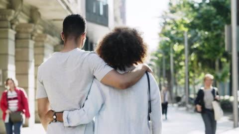 vidéos et rushes de femme de sourire regardant en arrière tout en marchant avec l'homme - jeune couple