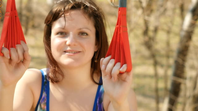 Smiling woman performs the aerogravity exercises Close-up. Young woman practicing aerogravity in the park. The woman is meditating with closed eyes on the ropes on tree. Flexible female hanging on the ropes and stretching her body and muscles. She's looking in camera and smiles. arthropod stock videos & royalty-free footage