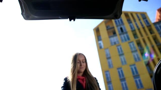 Femme souriante, mettre des sacs à provisions en coffre de voiture - Vidéo