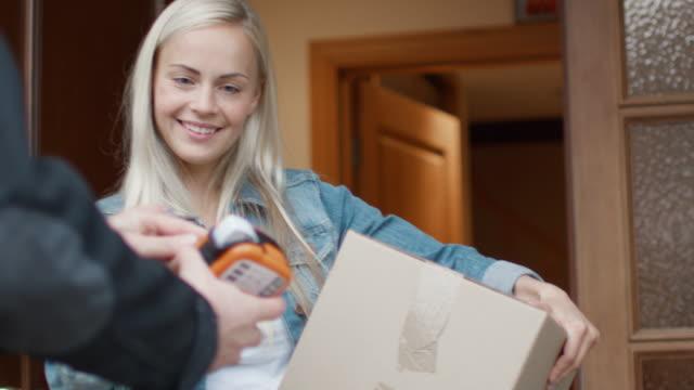 微笑的婦女在打開的門道上簽名電子簽名設備後收到郵政包裹 - postal worker 個影片檔及 b 捲影像