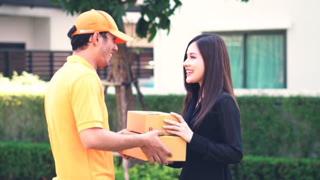 在花園裡站著的時候, 微笑的女人在簽名電子簽名裝置後收到郵包 - postal worker 個影片檔及 b 捲影像