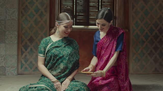 smiling woman serving indian food to female guest - sari filmów i materiałów b-roll