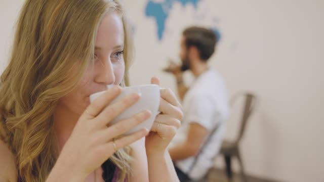 lächelnde frau trinkt kaffee - koffeinmolekül stock-videos und b-roll-filmmaterial