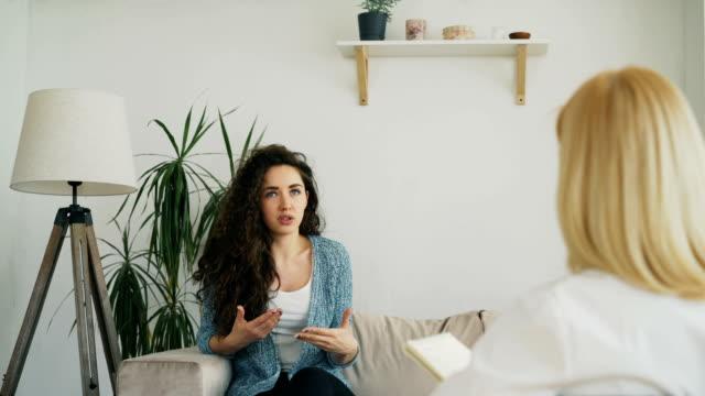 Femme souriante, assis sur le canapé et de parler aux femme psychanalyste dans son bureau à l'intérieur - Vidéo