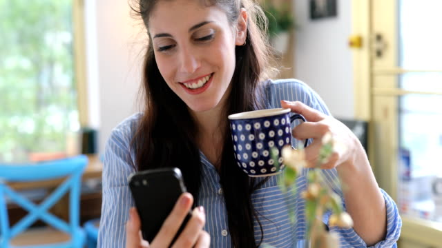 Smiling Woman Sitting With Smart Phone And Coffee video