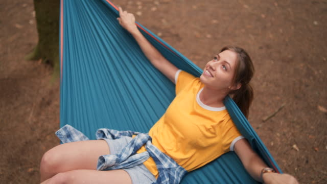 Smiling woman swinging in hammock