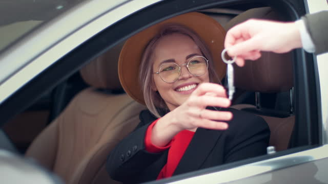 stockvideo's en b-roll-footage met glimlachende vrouw die sleutels aan haar nieuwe auto neemt - sleutel beveiligingsapparatuur