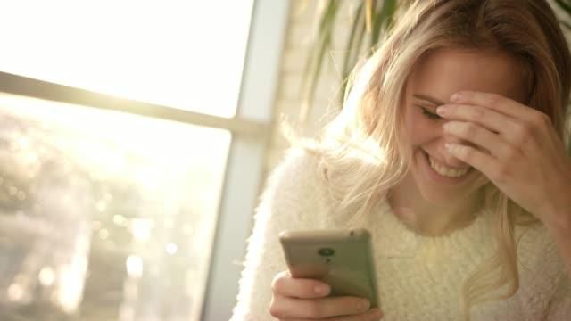 微笑的女人在智慧手機短信短信。快樂的女人短信手機 - 歡樂 個影片檔及 b 捲影像
