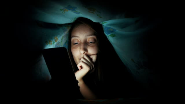 Smiling woman texting under blanket video