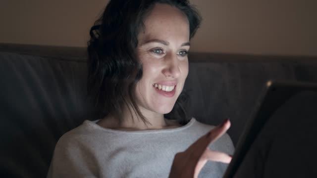 stockvideo's en b-roll-footage met lachende vrouw met behulp van digitale tablet bij nacht - een tablet gebruiken