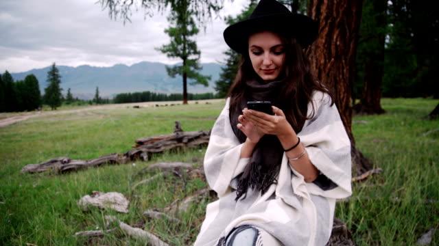 笑顔の女性を使用して携帯電話の公園で秋の ビデオ