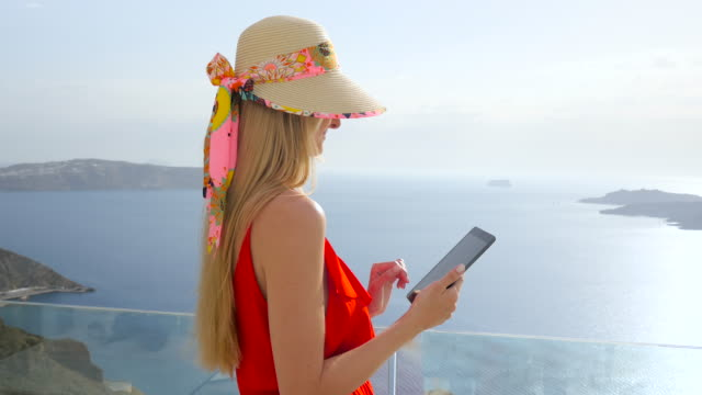 smiling woman using touchpad in santorini - travel agent stock videos and b-roll footage