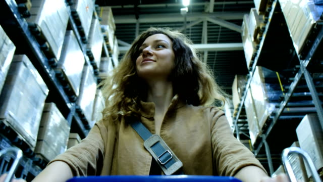 Smiling woman walks around the storage room with a trolley in a shopping center video