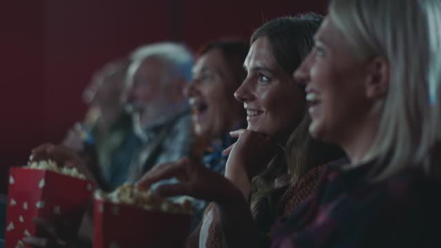 Smiling woman watching movie at cinema Smiling woman in row with other people watching movie at cinema film industry stock videos & royalty-free footage