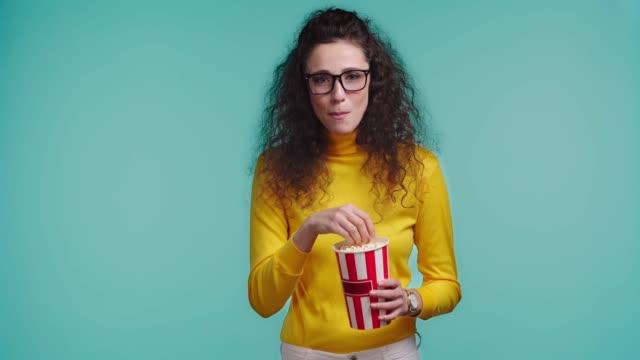 vídeos de stock, filmes e b-roll de mulher sorridente assistindo filme isolado em turquesa - balde pipoca