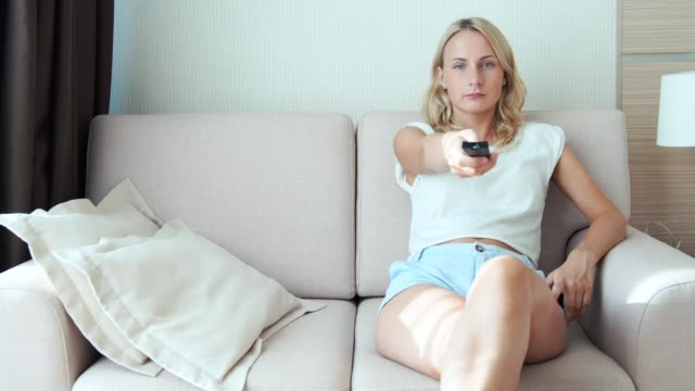 Smiling woman watching television in her living room video