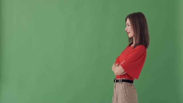 smiling woman with arms crossed over green screen - comparsa video stock e b–roll
